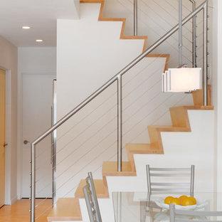 Inspiration pour un escalier design en U avec des marches en bois, des contremarches en bois et un garde-corps en câble.