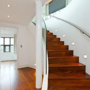 Foto på en funkis svängd trappa i trä, med sättsteg i trä och räcke i glas