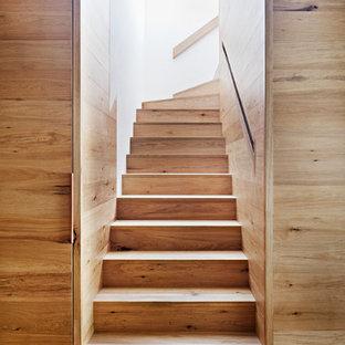 Imagen de escalera en L, contemporánea, de tamaño medio, con escalones de madera, contrahuellas de madera y barandilla de madera