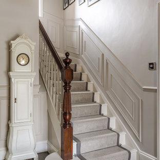 Идея дизайна: п-образная лестница среднего размера в классическом стиле с ступенями с ковровым покрытием, ковровыми подступенками, деревянными перилами и панелями на стенах