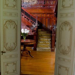 Inredning av en klassisk stor l-trappa, med heltäckningsmatta och sättsteg i trä