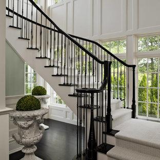 Стильный дизайн: изогнутая лестница в викторианском стиле с деревянными ступенями и крашенными деревянными подступенками - последний тренд