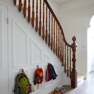 This is an example of a victorian painted wood l-shaped staircase in London with painted wood risers.