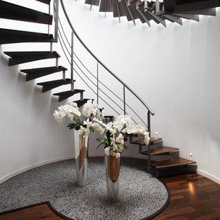 ロンドンの大きい木のコンテンポラリースタイルのおしゃれならせん階段 (金属の蹴込み板、金属の手すり) の写真