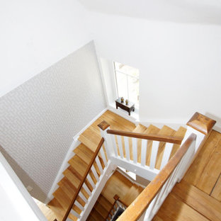 Immagine di una grande scala minimal con pedata in legno, alzata in legno, parapetto in legno e carta da parati