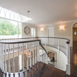 Staircase - large traditional wooden curved staircase idea in Philadelphia with wooden risers