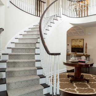 Imagen de escalera curva, clásica renovada, extra grande, con escalones de madera, barandilla de madera y contrahuellas de madera pintada
