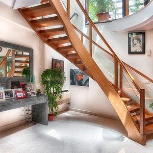 Imagen de escalera curva, actual, pequeña, sin contrahuella, con escalones de travertino y barandilla de vidrio