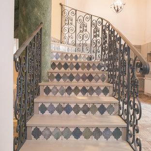 Modelo de escalera curva, de tamaño medio, con escalones de madera, contrahuellas con baldosas y/o azulejos y barandilla de metal