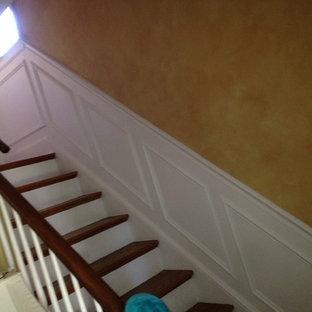 Imagen de escalera recta, de estilo americano, de tamaño medio, con escalones de madera, contrahuellas de madera pintada y barandilla de madera