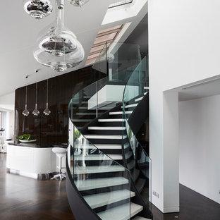 Idee per una scala curva moderna di medie dimensioni con pedata in marmo, alzata in metallo e parapetto in vetro