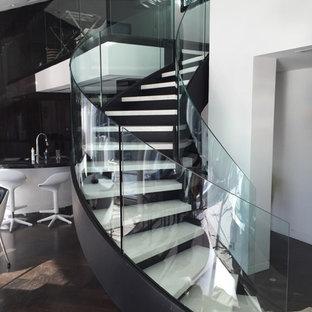 Foto di una scala curva moderna di medie dimensioni con pedata in marmo, alzata in metallo e parapetto in vetro