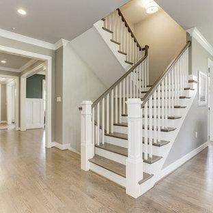 他の地域の大きい木のトランジショナルスタイルのおしゃれな折り返し階段 (フローリングの蹴込み板、木材の手すり) の写真