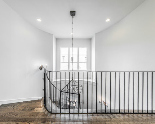This Is An Example Of A Large Mediterranean Wood Spiral Metal Railing  Staircase In Houston With