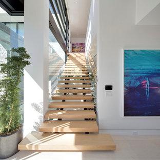 Свежая идея для дизайна: огромная прямая лестница в современном стиле с деревянными ступенями без подступенок - отличное фото интерьера