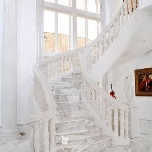 Idéer för en stor medelhavsstil svängd trappa i marmor, med sättsteg i marmor och räcke i trä
