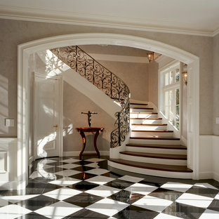 Imagen de escalera curva, clásica, grande, con escalones de madera, contrahuellas de madera pintada y barandilla de metal