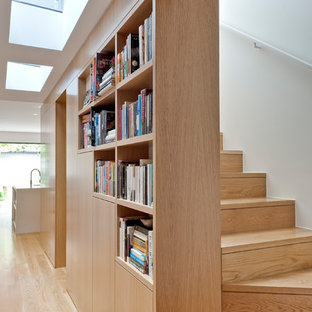 This is an example of a contemporary wood curved staircase in Sydney with wood risers and wood railing.