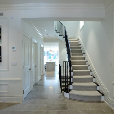 Example of a large classic wooden curved staircase design in New York with painted risers