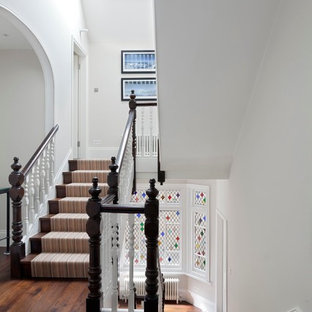 Photo of a large classic carpeted u-shaped wood railing staircase in London with carpeted risers.