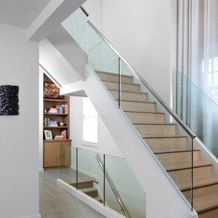 """Esempio di una grande scala a """"L"""" moderna con pedata in vetro, nessuna alzata, parapetto in metallo e carta da parati"""