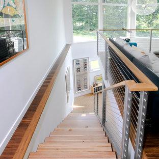 Esempio di una scala a rampa dritta minimal con pedata in legno e parapetto in cavi