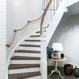 This is an example of a medium sized beach style wood curved wood railing staircase in London with painted wood risers.