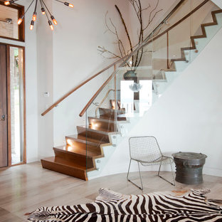Staircase - contemporary wooden curved glass railing staircase idea in Vancouver with wooden risers