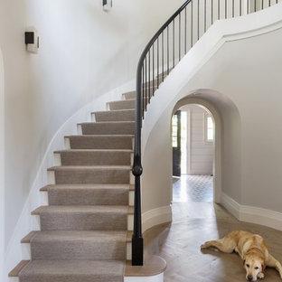 Modelo de escalera curva, tradicional renovada, de tamaño medio, con escalones de madera, contrahuellas de travertino y barandilla de madera