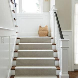 ボストンのカーペット敷きのトランジショナルスタイルのおしゃれな折り返し階段 (カーペット張りの蹴込み板、木材の手すり) の写真