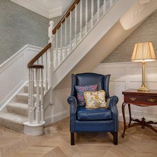 Imagen de escalera en L y boiserie, tradicional, grande, con escalones enmoquetados, contrahuellas enmoquetadas, barandilla de madera y boiserie