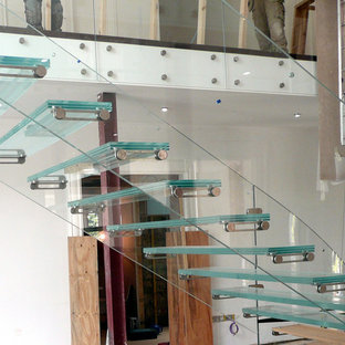 Example of a huge trendy glass floating glass railing staircase design in Other with glass risers