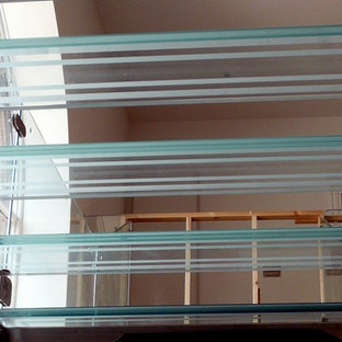 Huge trendy glass floating glass railing staircase photo in Other with glass risers
