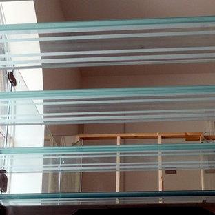 Foto di un'ampia scala sospesa design con pedata in vetro, alzata in vetro e parapetto in vetro