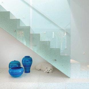 Modelo de escalera recta, minimalista, grande, con escalones de travertino, contrahuellas de travertino y barandilla de vidrio