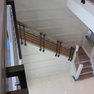 Foto de escalera en L y madera, tradicional renovada, grande, con escalones de madera, contrahuellas de madera, barandilla de varios materiales y madera
