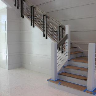 """Immagine di una grande scala a """"L"""" classica con pedata in legno, alzata in legno, parapetto in materiali misti e pareti in legno"""