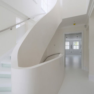 Staircase - small contemporary curved staircase idea in London with glass risers