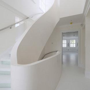 Imagen de escalera curva, contemporánea, pequeña, con contrahuellas de vidrio