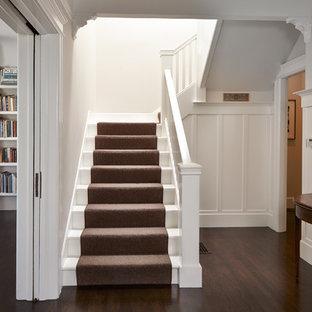 Modelo de escalera en U, clásica, de tamaño medio, con barandilla de madera, escalones de madera pintada y contrahuellas de madera pintada