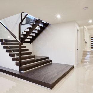メルボルンの中サイズの木のコンテンポラリースタイルのおしゃれな折り返し階段 (ガラスの蹴込み板、木材の手すり) の写真