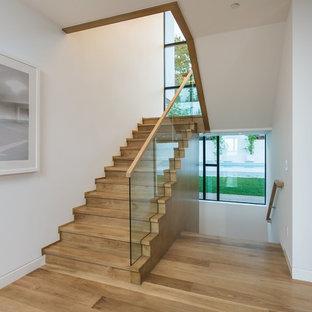 Ejemplo de escalera en U, actual, grande, con escalones de madera, contrahuellas de madera y barandilla de vidrio