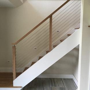Imagen de escalera en L, contemporánea, de tamaño medio, con escalones de madera pintada, contrahuellas de madera y barandilla de cable