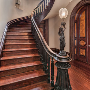 Large ornate wooden curved wood railing staircase photo in Other with wooden risers
