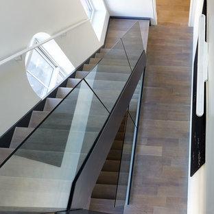 ニューヨークの広い木のモダンスタイルのおしゃれなフローティング階段 (木の蹴込み板、ガラスの手すり) の写真