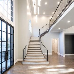 Ejemplo de escalera en L, clásica renovada, extra grande, con escalones de madera, barandilla de varios materiales y contrahuellas con baldosas y/o azulejos