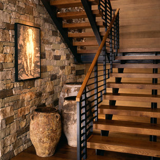 This is an example of a medium sized and mixed rustic wood u-shaped staircase in Denver with open risers.