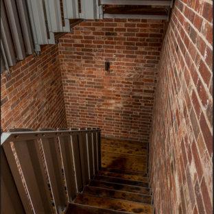 Foto de escalera en U y ladrillo, actual, de tamaño medio, sin contrahuella, con escalones de madera, barandilla de metal y ladrillo