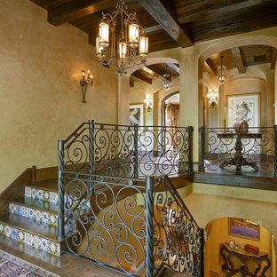 オーランドの大きい木の地中海スタイルのおしゃれな折り返し階段 (タイルの蹴込み板、金属の手すり) の写真