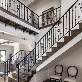 Imagen de escalera en L, mediterránea, grande, con escalones de madera, contrahuellas de madera y barandilla de metal